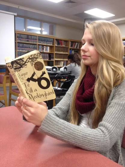Freshman Julia Hader reads To Kill A Mockingbird in the library.