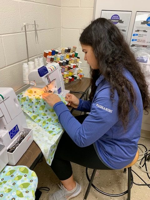 Julia Magnanini, FCCLA co-president, sewing fabric together to create a port pillow.  Provided by Jacquelyn Berg, FCCLA adviser.