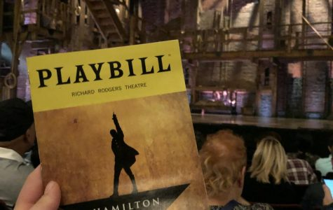 A Hamilton playbill is held up in front of the Richard Rodgers Theatre in New York City
