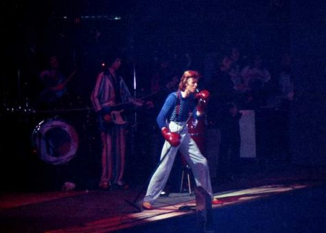 David Bowie performs at Charlotte Park Center, NC in 1974. wearing boxing gloves and high waisted pants.