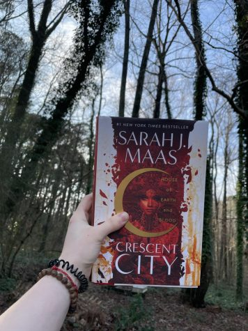 A hand holding House of Earth and Blood, Sarah J. Mass, in the woods.