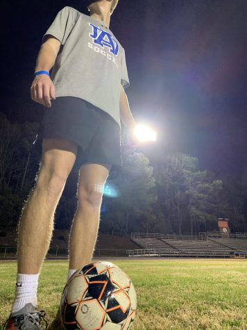 Sean Herbst, senior, stands over a corner kick during crossing drills in the soccer team