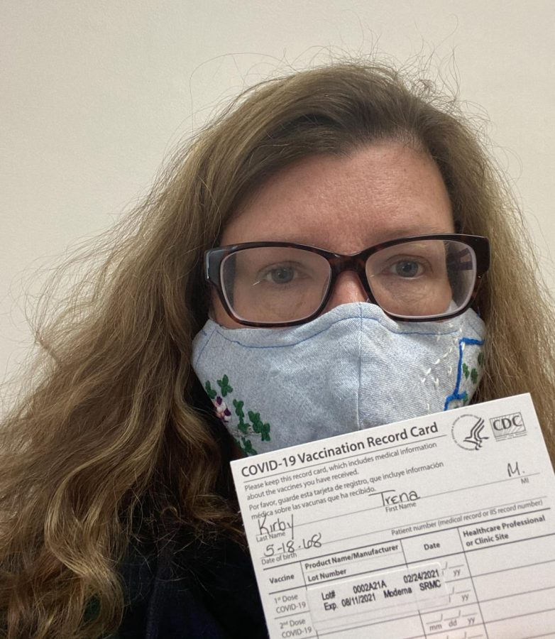 Trena Kirby, AP Human Geography and AP Government & Politics teacher at Athens Drive wears a mask and poses with her vaccination card for receiving the Moderna vaccine.