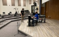 Micheal Santangelo, chorus teacher, and cast member Will Wakeford rehearse one of his songs for the production.