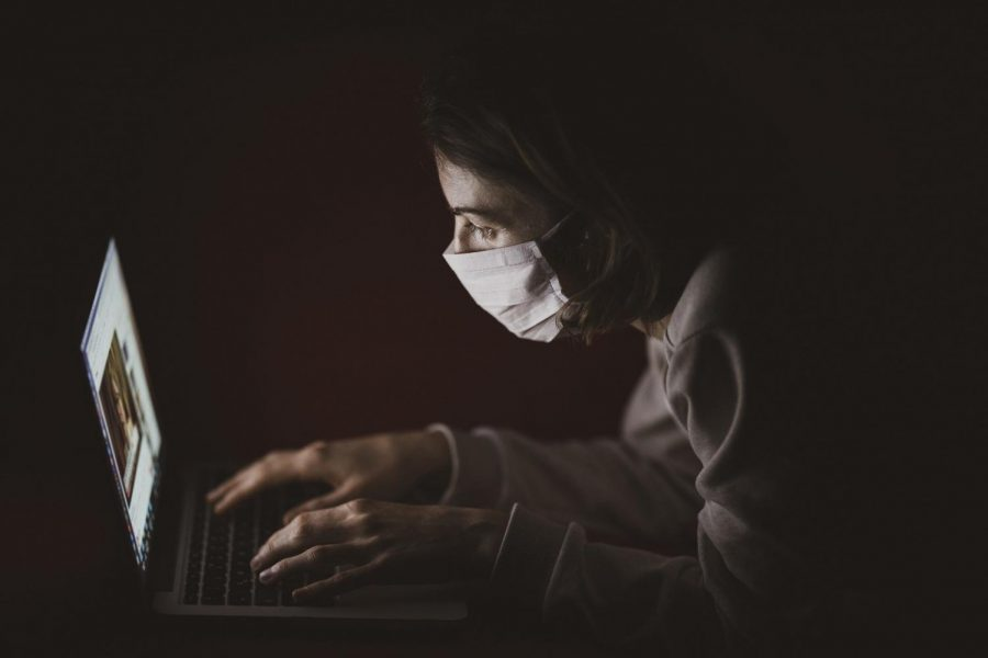 A student in a dark room wearing a covid-19 mask, staring at her computer screen.