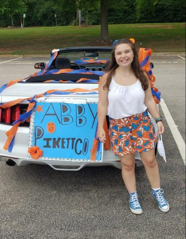 Senior Abby Pikett stands next to her decorated car at the Senior Drive Through at Athens Drive.