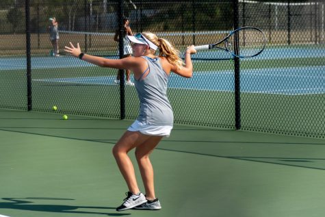 Cassidy returns serve during match at Green Level High School.
