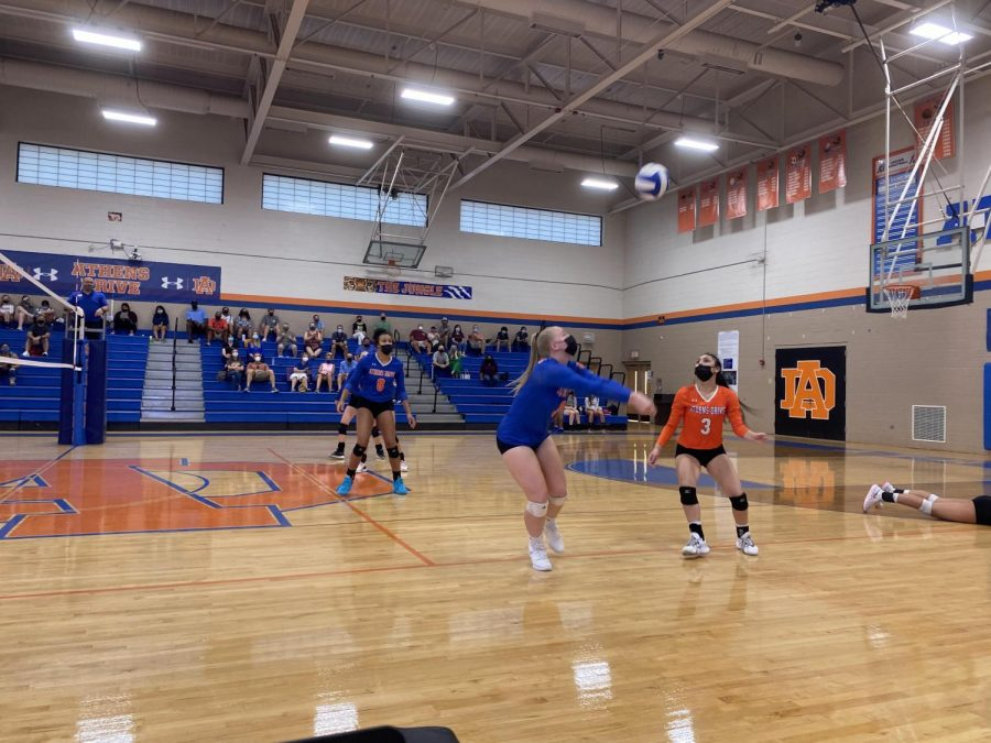Varsity volleyball players pass the ball after Sammie Blough, junior, dives to keep the ball alive